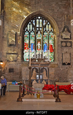 An ornate stained glass window within the Church of St John the Baptist in the market square of Cirencester with a stone font in the foreground. - Stock Photo