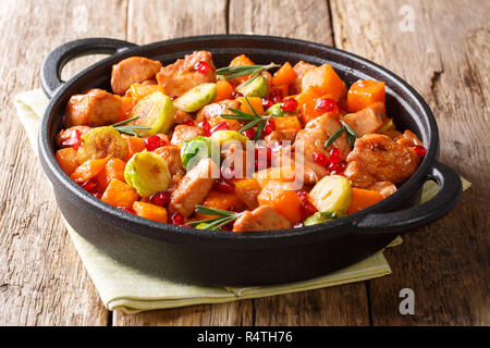 Spicy tasty chicken with vegetables with pomegranate sauce close-up in a frying pan on the table. horizontal - Stock Photo