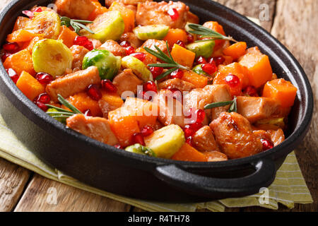 Organic food chicken pieces with vegetables and rosemary in pomegranate sauce close-up in a frying pan on the table. horizontal - Stock Photo