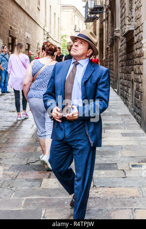 Barcelona, Spain - 4th October 2017: Elegantly dressed man admiring the old buildings in the Gothic quarter. Tourists flock to this area of the city. - Stock Photo