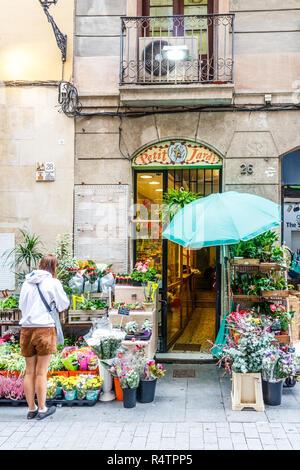 Barcelona, Spain - 4th October 2017: Woman outside a florists shop, La Rambla. The area has many small, specialist shops. - Stock Photo