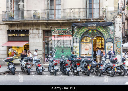 Barcelona, Spain - 4th October 2017: Motorbikes parked outside shops on Las Ramblas. The street is  very famous pedestrianised shopping area. - Stock Photo