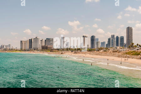 People on the beach, Alma Beach, view of skyline of Tel Aviv with skyscrapers, Tel Aviv, Israel - Stock Photo