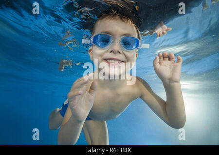 Young boy wearing swimming goggles dives in a pool - Stock Photo