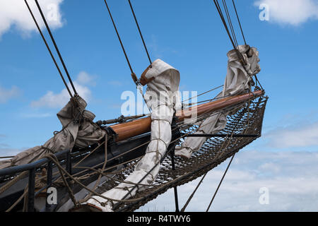 bowsprit and jib boom with reefed sails on the bow of a historic sailing ship against a blue sky with clouds - Stock Photo