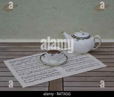 English teacup with saucer and teapot, fine bone china porcelain, on a sheet of music - Stock Photo