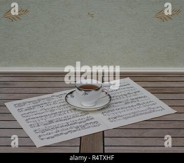 English teacup with saucer, fine bone china porcelain, on a sheet of music - Stock Photo