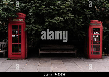 Two iconic red telephone boxes designed by Sir Giles Gilbert Scott, London, UK. - Stock Photo
