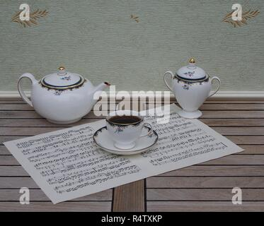 English teacup with saucer, teapot and sugar bowl, fine bone china porcelain, on a sheet of music - Stock Photo
