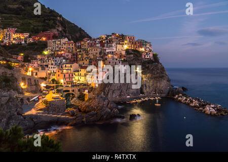 The small italian city Manarola over the sea at nighttime - Stock Photo