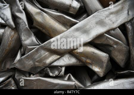 Crushed, smashed, compressed stainless steel metal pipes for scrap metal recycling. - Stock Photo
