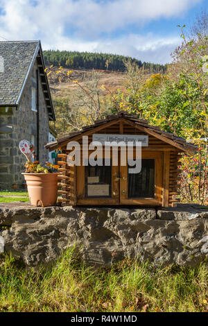 Little Free Library (roadside community Library) on the front garden wall of a house in Tomich, Highland Region, Scotland - Stock Photo