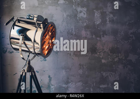 theater spot light with smoke against grunge wall. - Stock Photo