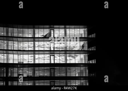 A lone figure walks along the balcony of an empty office building at night in Bristol in the united Kingdom. - Stock Photo