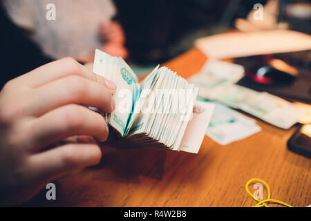 Male hand holds a thick stack of cash money. Million Russian rubles. The concept of rich, wealth, profits, business and finance. Five thousandth bills banknotes. A lots wads of money. - Stock Photo