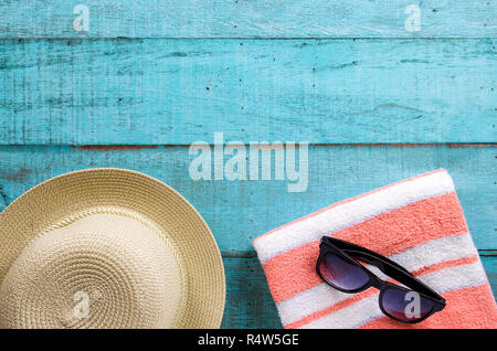 Summer holiday background. Straw hat, towel and sunglasses on blue wooden table. - Stock Photo