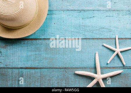 Summer holiday background. Straw hat and starfish on blue wooden table. - Stock Photo