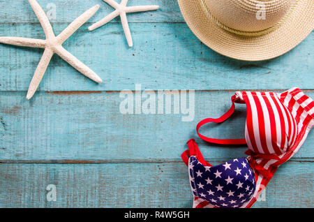 Summer holiday background. Straw hat, swimsuit and starfish on blue wooden table. - Stock Photo