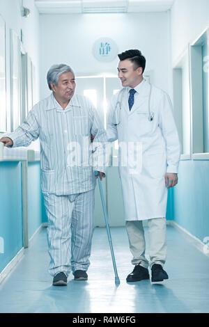 Doctors and older men in the hospital corridor - Stock Photo
