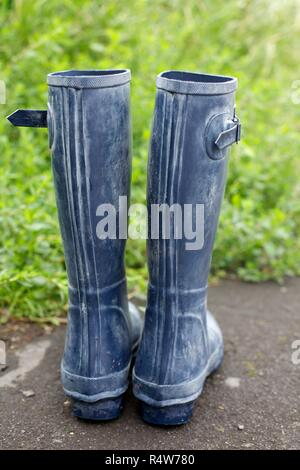 Rubber Wellington boots in the garden - Stock Photo