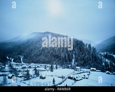 Aerial view of foggy countryside and houses in snowy valley. Hills and mountains with pine tree forest covered in snow. Multi-layered mountain landscape. Ski resort and traveltheme. Moody weather. - Stock Photo
