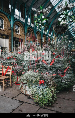 London, UK - November 21, 2018: Christmas trees and decorations in Covent Garden Market, one of the most popular tourist sites in London, UK. - Stock Photo