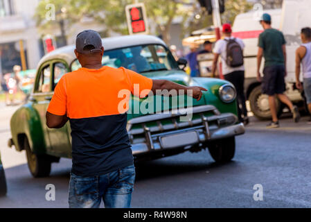 Cuban man raising hand calling a collective taxi in Old Havana. Young Afro Cuban man hailing a traditional shared taxi on the street. - Stock Photo