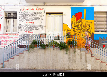 A girl walks on a staircase of a painted house in the village of Orgosolo, Nuoro province, Sardinia, Italy, Europe. - Stock Photo