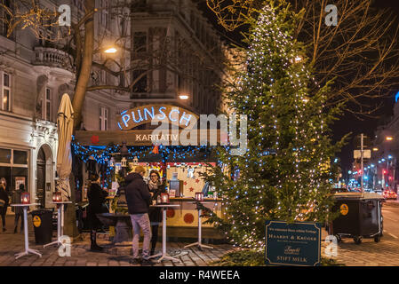Vienna, Austria - December 25, 2017. People drink mulled wine in front of traditional Viennese Christmas stall booth selling punch. Hot drinks stand a - Stock Photo