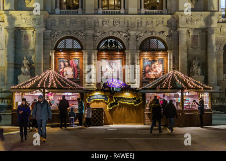 Vienna, Austria - December 25, 2017. People walking at traditional Viennese Christmas market with stall booth at Maria-Theresien-Platz. Kiosks and sta - Stock Photo