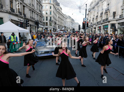 The elite song and dance troop 'The West End Kids', performing to  tunes from the 'Back to he Future Films, in front of the DeLorean Time Machine - Stock Photo