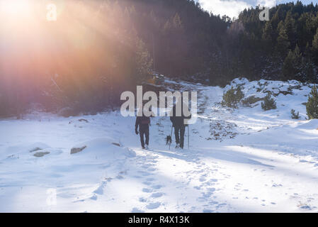 Canillo, Andorra: November 27, 2018: Two young people with cahorro walking along a beautiful path in the first autumn snow in Bordes de Envalira, Cani - Stock Photo