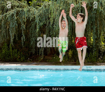 Two boys jumping into a swimming pool. - Stock Photo