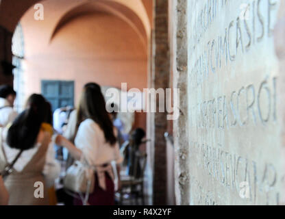 Latin inscription engraved on the wall of the Church of Santa Maria in Cosmedin in Rome, Italy. On background some visitors are waiting to see the mou - Stock Photo