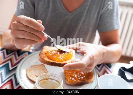 closeup of a young caucasian man, wearing a casual gray T-shirt, sitting at a set table, spreading some orange or peach jam on a toast - Stock Photo