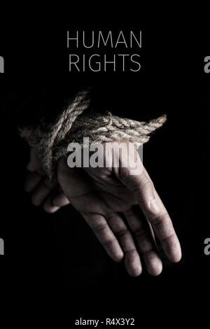 closeup of a man with his hands tied behind his back with rope, and the text human rights against a black background - Stock Photo