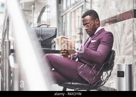 A beautiful African American businessman reads a menu in a cafe - Stock Photo
