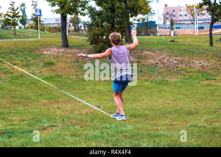 A young man in a public park learning to walk a tightrope. Slacklining is a practice in balance that typically uses nylon or polyester webbing tension - Stock Photo