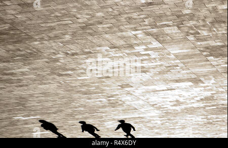 Blurry shadow silhouettes of  people walking the empty city square - Stock Photo