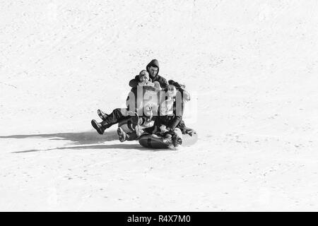 Adygea, Russia - January 23,  2017: Young happy couple with children riding on inflatable sledding tubing on a snowy slope, a man shoots a video on a  - Stock Photo
