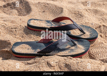 A Close up view of a pair of blue and red slops in the beach sand on a sunny summers day