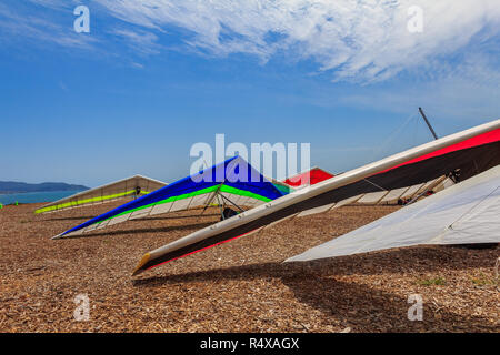Colorful hang gliding wings lined up on top of a cliff at Fort Funston in San Francisco, one of the premier hang-gliding spots in the country - Stock Photo