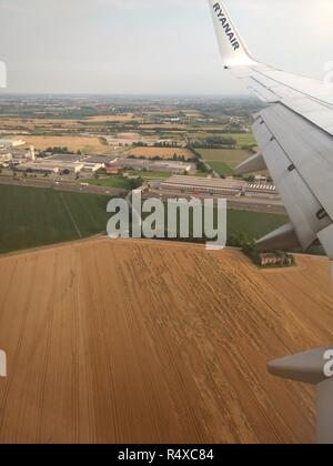 An aerial view of the Bergamo countryside, with plowed and planted fields, industrial warehouses and streets, with a blue sky with clouds, in Italy - Stock Photo