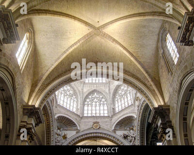 The main dome with stained glass windows and decorated pointed arches and the pointed vault in the gothic Saint Mary's Cathedral in Valencia, Spain - Stock Photo