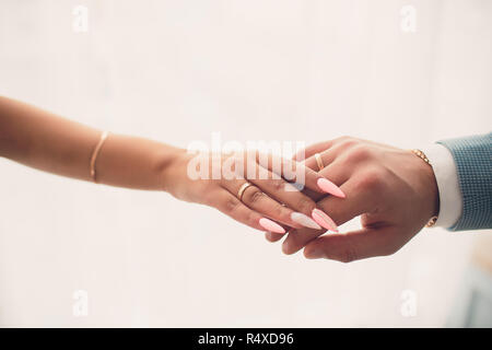 Newlyweds holding hands, their weddingbands showing.White background. - Stock Photo