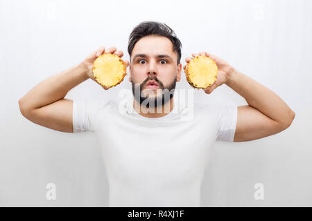 Really amazed young man stand and look on camera. He coveres ears with two halfs of one pineapple. Guy is scared and amased. Man in distracted. Isolated on white background. - Stock Photo