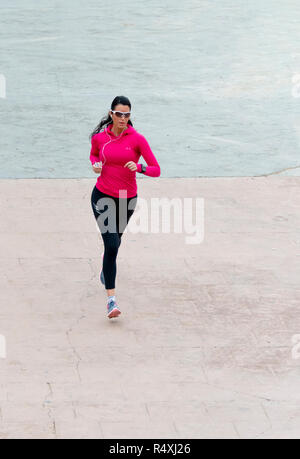 Attractive young woman in pink top and sunglasses keeping fit jogging - Stock Photo
