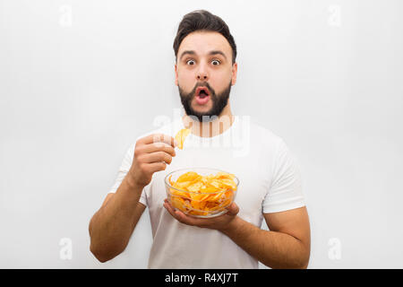 Excited and amazed young bearded man stand and look at camera. He holds bowl with chips in one hand and one piece of unhealthy product in another one. Isolated on white background. - Stock Photo
