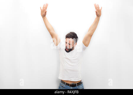 Very happy young man stands and looks down. He keeps hands up. Guy is amazed. Isolated on white background. - Stock Photo