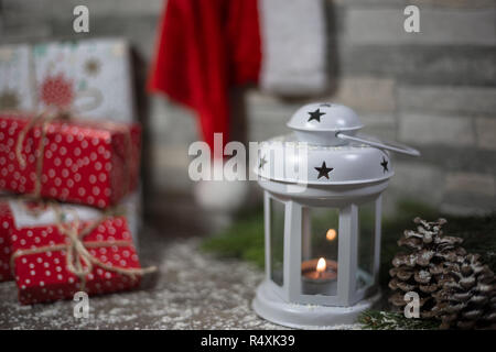Christmas background with lantern light, gifts and Santa Claus hat hanging on wall. Xmas concept. - Stock Photo
